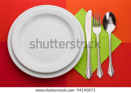 White empty plate with fork, spoon and knife on a red tablecloth - stock photo