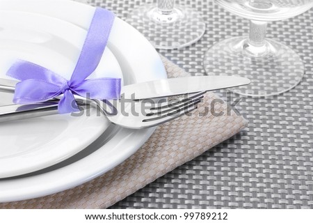 White empty plates, fork and knife tied with a ribbon and glasses on a grey tablecloth