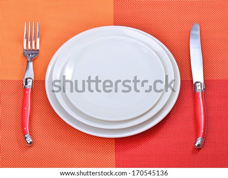 White empty plates with fork and knife on a red placemats - stock photo
