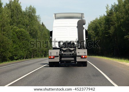 White empty semitrailer truck goes on the road