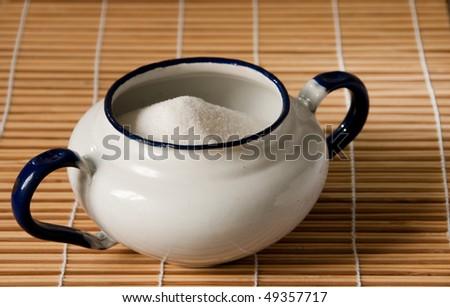 white enamel sugar bowl on a straw mat - stock photo