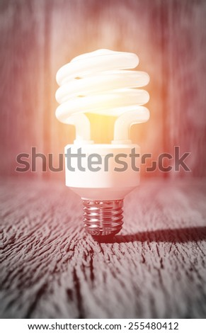 white energy saving bulb, Illuminated light bulb, CFL bulb, Realistic photo image on wood background;lighting effect vintage style - stock photo