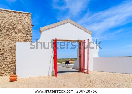 White entrance gate to Cabo Sao Vicente lighthouse on coast of Portugal near Lagos - stock photo