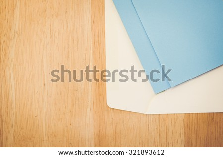 white envelope and blue writing paper on a natural wood surface