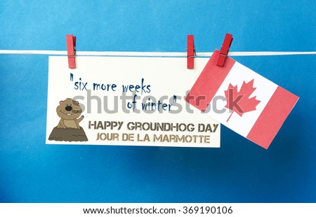 White envelope, cute face groundhog and text Happy Groundhog Day - 6 more weeks of winter. Canada flag hanging on clothespin. Jour de la Marmotte - Groundhog Day Canadian on French. Toned image