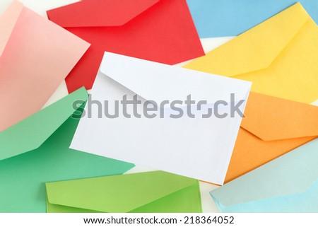 White envelope on the colorful envelopes - stock photo
