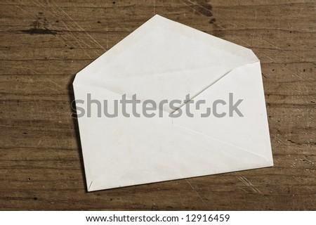 White envelope on wooden table, open, studio shot. - stock photo