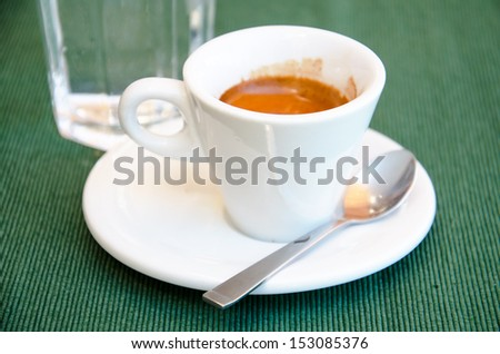 White espresso cup and a glass of cold water standing on the green textile tablecloth - stock photo