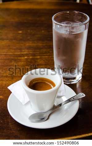 White espresso cup with glass of cold water standing on the wooden table - stock photo
