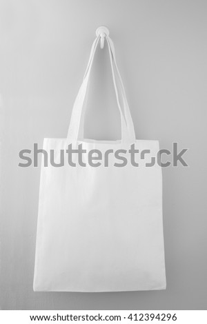 White fabric bag hanging on the gray wall - stock photo