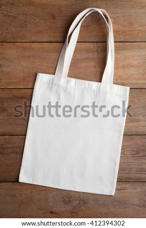 White fabric bag on wooden table - stock photo