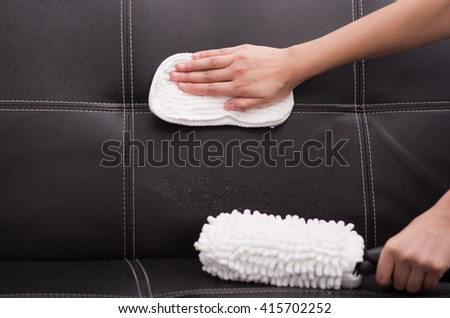 White fabric brush from steam cleaning machine being used on black leather couch, hand rubbing sofa with cloth - stock photo