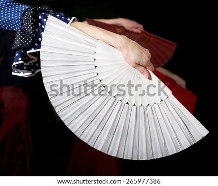 White fan and fragment of woman hand in flamenco performance, fragment photo of flamenco dancer, spanish fan, flamenco - stock photo