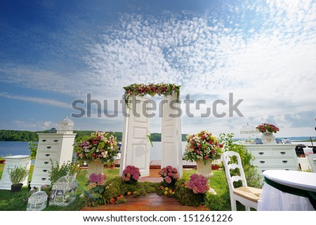 White fancy door as a wedding arch decorated with flowers - stock photo