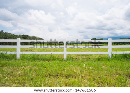 white fence in farm field and overcast sky - stock photo