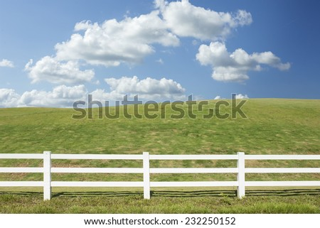 white fence in farm field with blue sky