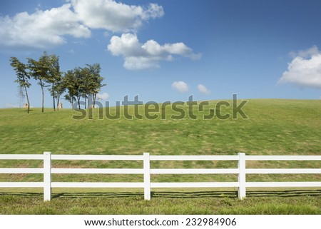 white fence in green farm field with blue sky - stock photo