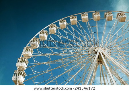 White ferris wheel in a fair and amusement park under blue sky - stock photo