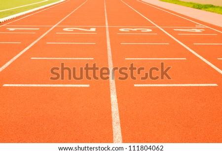 White finish line on the orange track and field tartan - stock photo