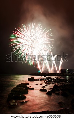 White fireworks launched at the shoreline of the harbor - stock photo