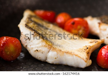 White fish fillet of perch, cod with tomato on fried pan - stock photo
