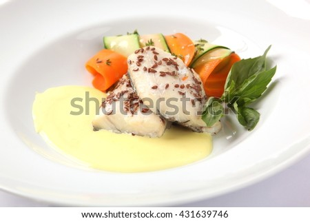 White fish on a plate with yellow sauce - stock photo
