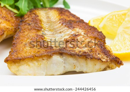 White fish with lemon and arugula on white plate, selective focus - stock photo