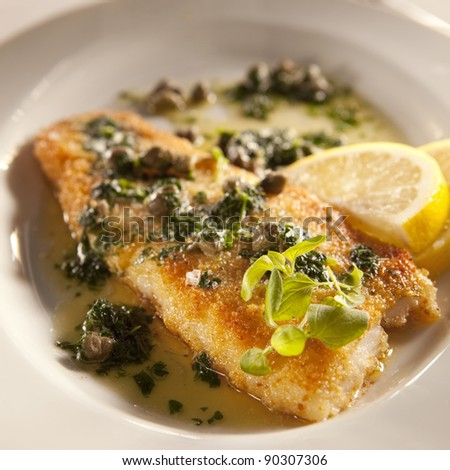 White fish with lemon and capris-olive oil dressing - stock photo