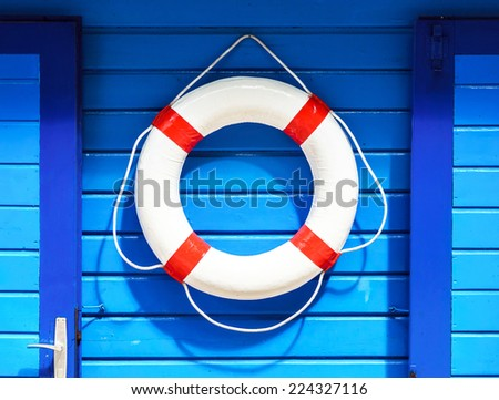 White flotation ring on the blue wall near boat rental - stock photo
