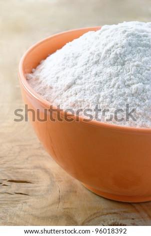 white flour in the orange bowl on the table - stock photo