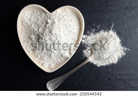 White flour on a black, stone table. - stock photo