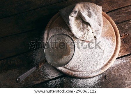 White flour on cutting board on wooden table background - stock photo