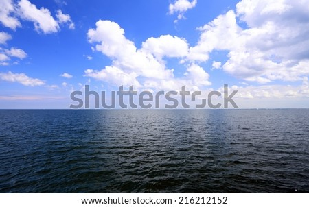 White fluffy clouds blue sky above a dark surface of the sea - stock photo