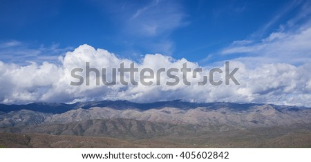 White Fluffy Clouds Over the Mountains - stock photo