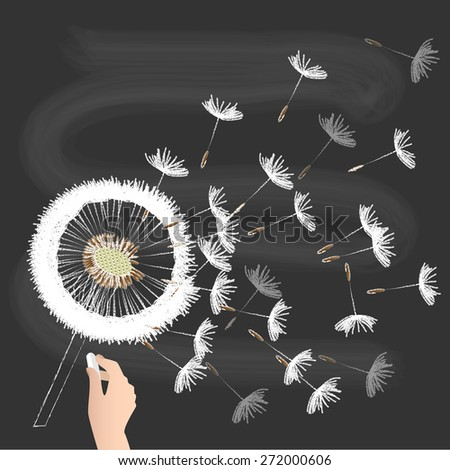 white, fluffy dandelion with flying seeds on the blackboard - stock photo