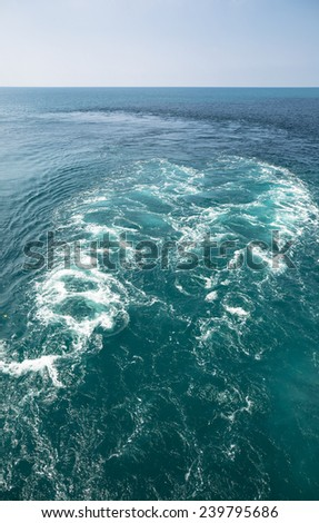 White foam and blue sea at back of big ship - stock photo
