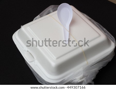 WHITE FOAM-BOX FOR FAST-FOOD PACKING WITH PLASTIC SPOON IN THE PLASTIC BAG - stock photo