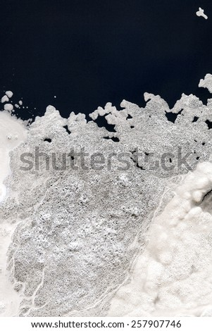 White foam with open patches of water, vertical image. - stock photo