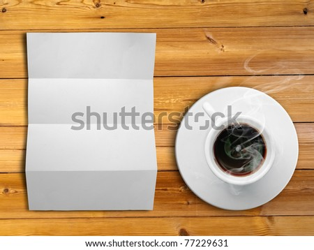 White fold paper and a white coffee cup on a wooden desk - stock photo