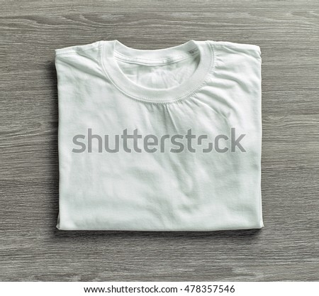 white folded shirt on grey wood background, top view