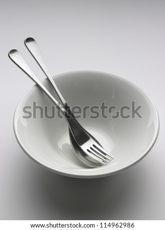 White food bowl with a spoon and fork on a neutral background