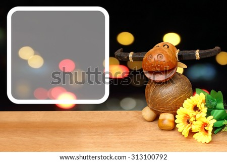 white frame and buffalo wooden model and yellow flower with bokeh from traffic light and car background - stock photo