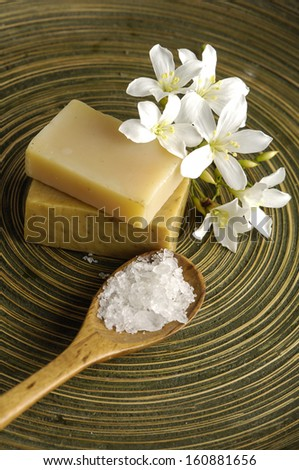 White frangipani and stacked soap with salt in spoon on wooden plate