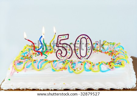 White frosted birthday cake with lit candles and the number 50 on top. - stock photo