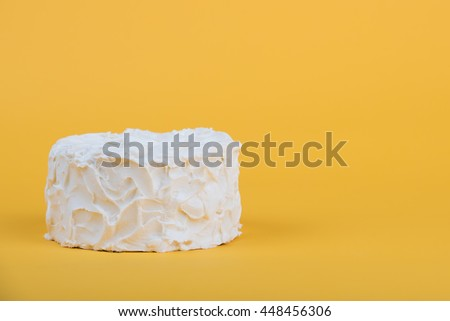 White frosted cake on yellow background - stock photo