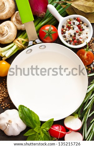 White frying pan with copy space for note or recipe surrounded by food ingredients. - stock photo