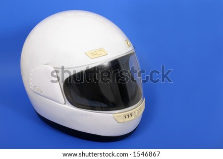 White full face motorcycle helmet on a blue background. - stock photo