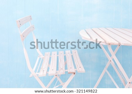 White garden table and chairs in blue background