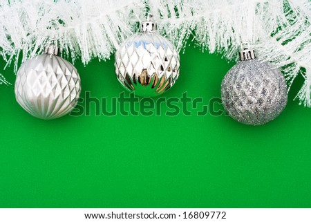 White garland on green background with silver glass balls, Christmas background