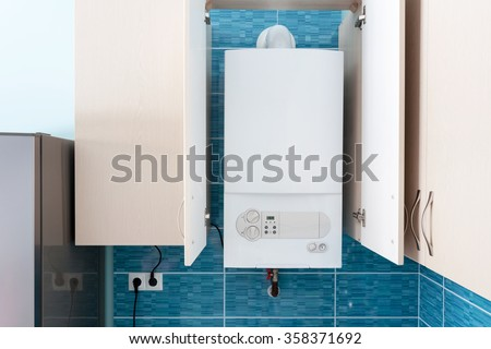 White gas boiler mounted in wall cupboard - stock photo